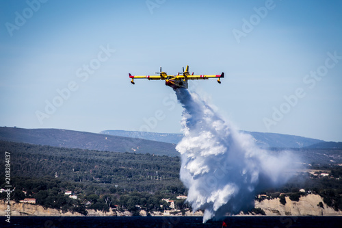 Fototapeta yellow red fire fighting plane throwing a cloud of water