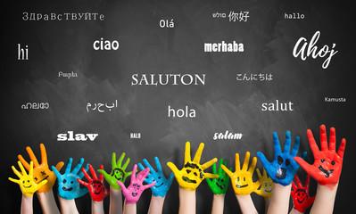 Viele Kinderhände vor Wandtafel mit dem Wort