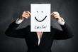 Leinwanddruck Bild - junge Geschäftsfrau hält Schild mit Smiley vor ihr Gesicht