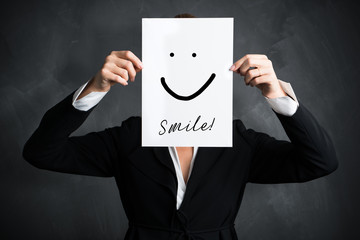 junge Geschäftsfrau hält Schild mit Smiley vor ihr Gesicht