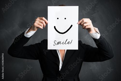 Leinwanddruck Bild junge Geschäftsfrau hält Schild mit Smiley vor ihr Gesicht