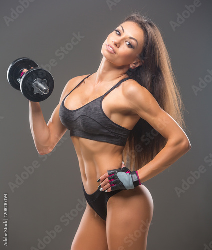 Poster Beautiful young sexy woman bodybuilder, in sportswear uses sports equipment, posing in front of the camera. Idyllic figure, beautiful waist, biceps, triceps. Motivation.