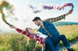 Leinwanddruck Bild - side view of man with colorful smoke bombs holding girlfriend back in rural field
