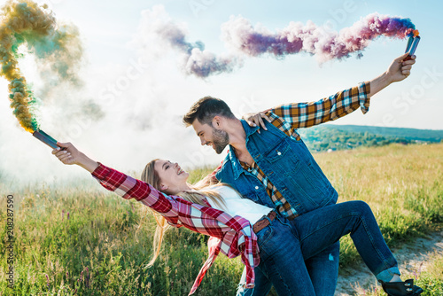Leinwanddruck Bild side view of man with colorful smoke bombs holding girlfriend back in rural field