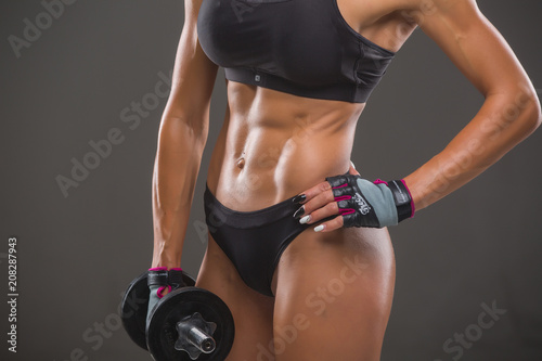 Sticker Beautiful young sexy woman bodybuilder, in sportswear uses sports equipment, posing in front of the camera. Idyllic figure, beautiful waist, biceps, triceps. Motivation.