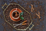 Cup of coffee on tray with coffee beans on black table background. |Top view, close up. - 208290355