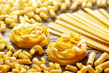 Tagliatelle nests and pasta on a wood background - 208293114
