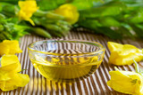 A bowl of evening primrose oil with fresh blooming evening primrose plant