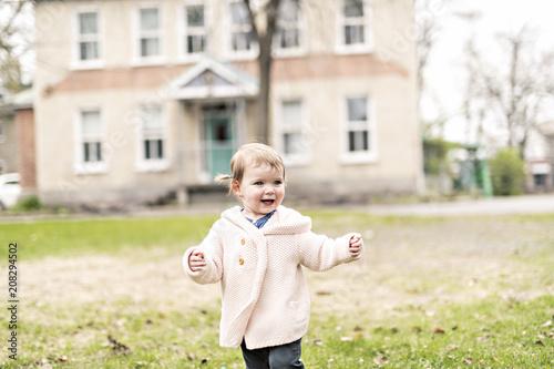 Leinwanddruck Bild Smiling little girl outside wearing in pink
