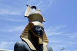 A large beautiful stone statue of a black proud majestic pharaoh in a golden cap, a crown in the shape of a jug against a blue sky in Egypt.