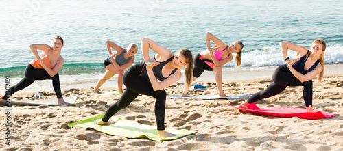 Females exercising yoga positions on beach