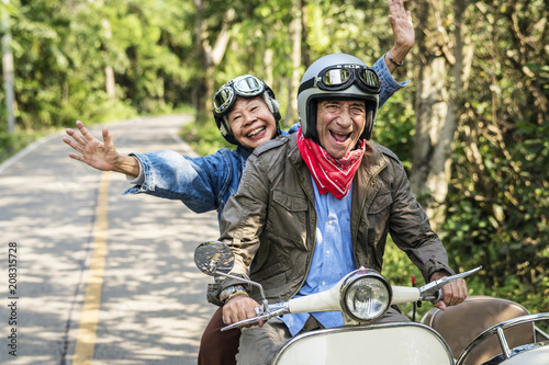 Leinwandbild Motiv Senior couple riding a classic scooter