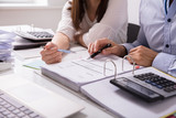 Two Businesspeople Checking Invoice - 208323760