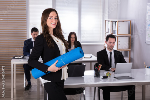 Businesswoman Walking With Exercise Mat