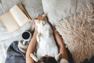 Hygge concept with cat, book and coffee in the bed