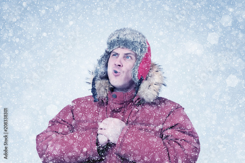 Frozen man in red winter clothes lets the steam out of his mouth, cold, snow, blizzard