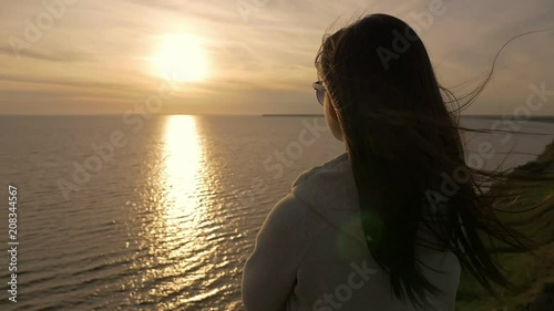 Back view of a romantic girl with long loose hair in a white suit standing on the Black Sea beach and looking at sparkling sunset in summer