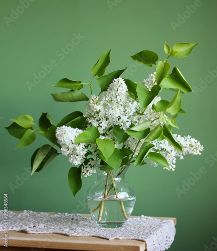 White lilac. Bouquet of flowering branches in a vase.