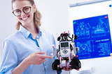 Modern engineering. Joyful smart female engineer holding a robot and smiling while being happy about successful invention - 208355100