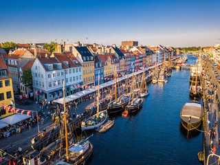 Amazing historical city center. Nyhavn New Harbour canal and entertainment district in Copenhagen, Denmark. The canal harbours many historical wooden ships. Aerial view from the top.