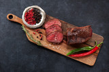 Roast beef on a cutting wooden board with rosemary and chili pepper, on a concrete black background, top view - 208359943