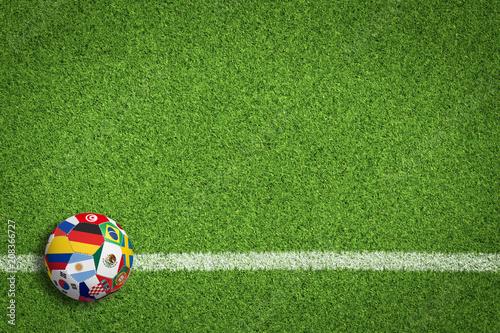 Leinwanddruck Bild Fußball auf Rasen / Spielfeld mit Länderflaggen