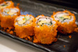 California maki sushi roll on black plate, japanese food