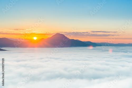 Fotobehang Zee zonsondergang beautiful sunrise over mountain with fog