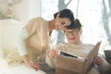 Smiling senior woman watching photobook - 208391517