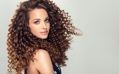 Brunette  girl with long  and   shiny curly  hair .  Beautiful  model woman  with wavy hairstyle  © edwardderule
