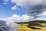 Solar Power Station on the spring Meadow with cloudy Sky  - 208398982
