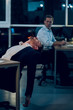 Office worker having little nap in his chair at table. Young businessman sitting in chair with his body bent backwards and his hands down. His coworker looking at him in background. - 208402571