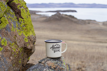 Aluminum enameled mug of a traveler with hot tea on a moss-covered mountain on a picturesque background of Lake Baikal in late spring on a cloudy day.