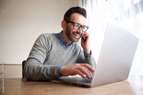 smiling businessman talking on cellphone and working on computer - 208405194