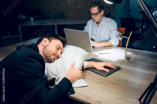 Foto Murales Young man fell asleep in office at night. Good looking businessman resting his head on pillow on brown wooden office desk. His coworker sitting with laptop working in background.