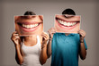 Leinwanddruck Bild - happy couple holding a picture of a mouth smiling on a gray background