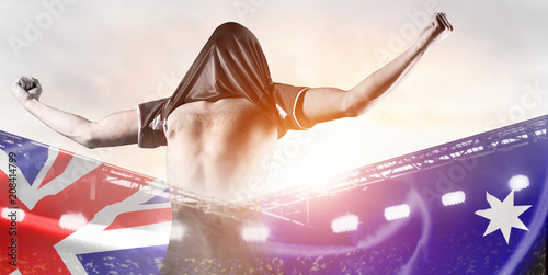 Australia national team. Double exposure photo of stadium and soccer or football player celebrating goal with his jersey on head