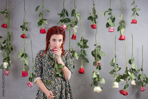 Girl with red hair among hanging roses