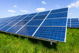 Solar panel on blue sky background. Green grass and cloudy sky. Alternative energy concept - 208445939