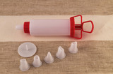 A set for the confectioner is a syringe for extruding the cream and a set of nozzles.