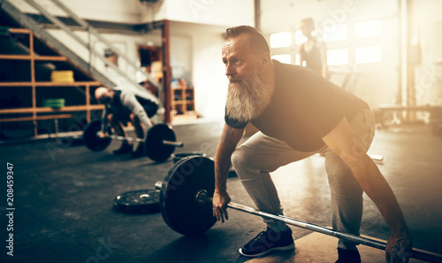 Focused mature man preparing to lift weights during a workout