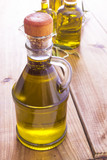 bottles of extra virgin oil on wooden background - 208466779