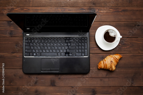 Fotobehang Chocolade laptop and hot chocolate with croissant for Breakfast