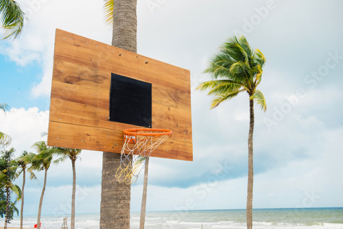 Fotobehang Basketbal Basketball equipment on tropical island. Empty basket. Outdoor sport game. Active lifestyle in summer vacation. Streetball playing. Basketball in palm garden. Basketball field. Sunny day outside