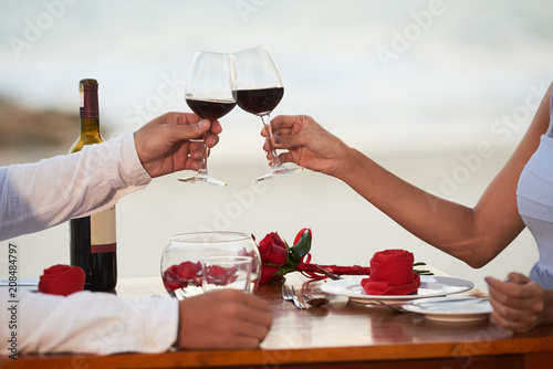 Close-up shot of young couple sitting at table of beach restaurant and clinking wine glasses together while celebrating momentous event, blurred background