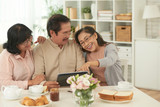 Three friends remember their happy moments on touchpad at the table at home - 208485508