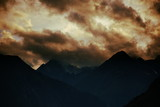 Forbidding pointy mountains under dramatic sunset clouds