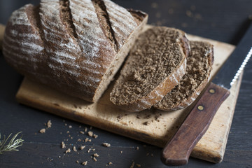 Closeup of sliced whole grain bread on wooden cutting board; selective focus.