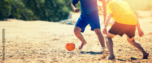 playing beach soccer - 208503158
