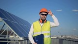 Rooftop with a solar panel and an engineer lifting his hardhat on it - 208504191